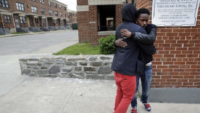 Ronte Jenkins, right, a lifelong friend of Freddie Gray, hugs a friend at the site of Gray's arrest, back left, Friday, May 1, 2015, in Baltimore, after the announcement of charges against the police officers involved in Gray's arrest. (AP...