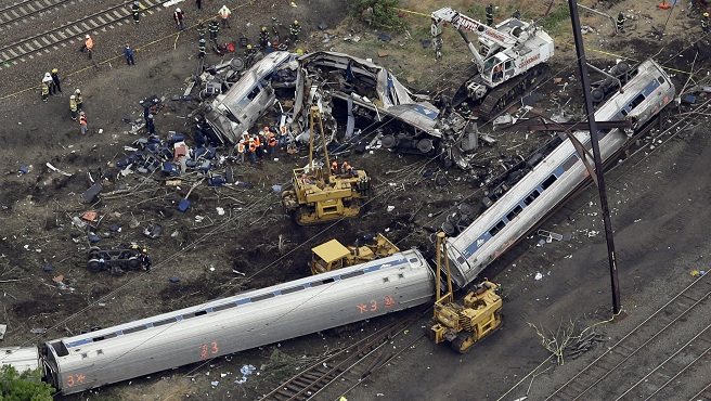 Emergency personnel work at the scene of a deadly train derailment, Wednesday, May 13, 2015, in Philadelphia. The Amtrak train, headed to New York City, derailed and crashed in Philadelphia on Tuesday night, killing at least six people and...