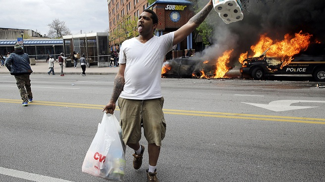 A man carries items from a store as police vehicles burn, Monday, April 27, 2015, after the funeral of Freddie Gray in Baltimore. Gray died from spinal injuries about a week after he was arrested and transported in a Baltimore Police Department...