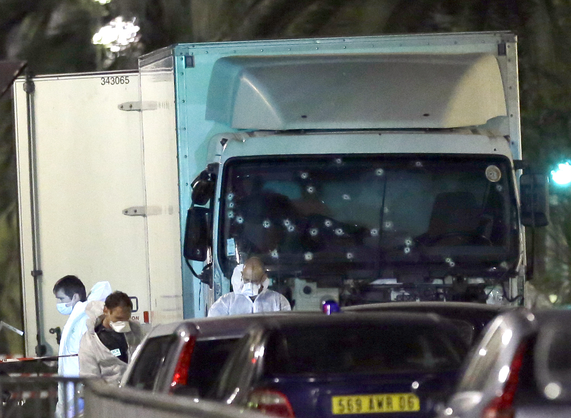 Forensic officers stands near a truck with its windscreen riddled with bullets, that plowed through a crowd of revelers who'd gathered to watch the fireworks in the French resort city of Nice, southern France, Friday, July 15, 2016. At least 80...