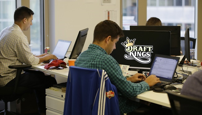 In this Wednesday, Sept. 9, 2015, photo, Bear Duker, a marketing manager for strategic partnerships at DraftKings, a daily fantasy sports company, works at his computer in Boston. The daily fantasy sports industry is eyeing a breakout season as...