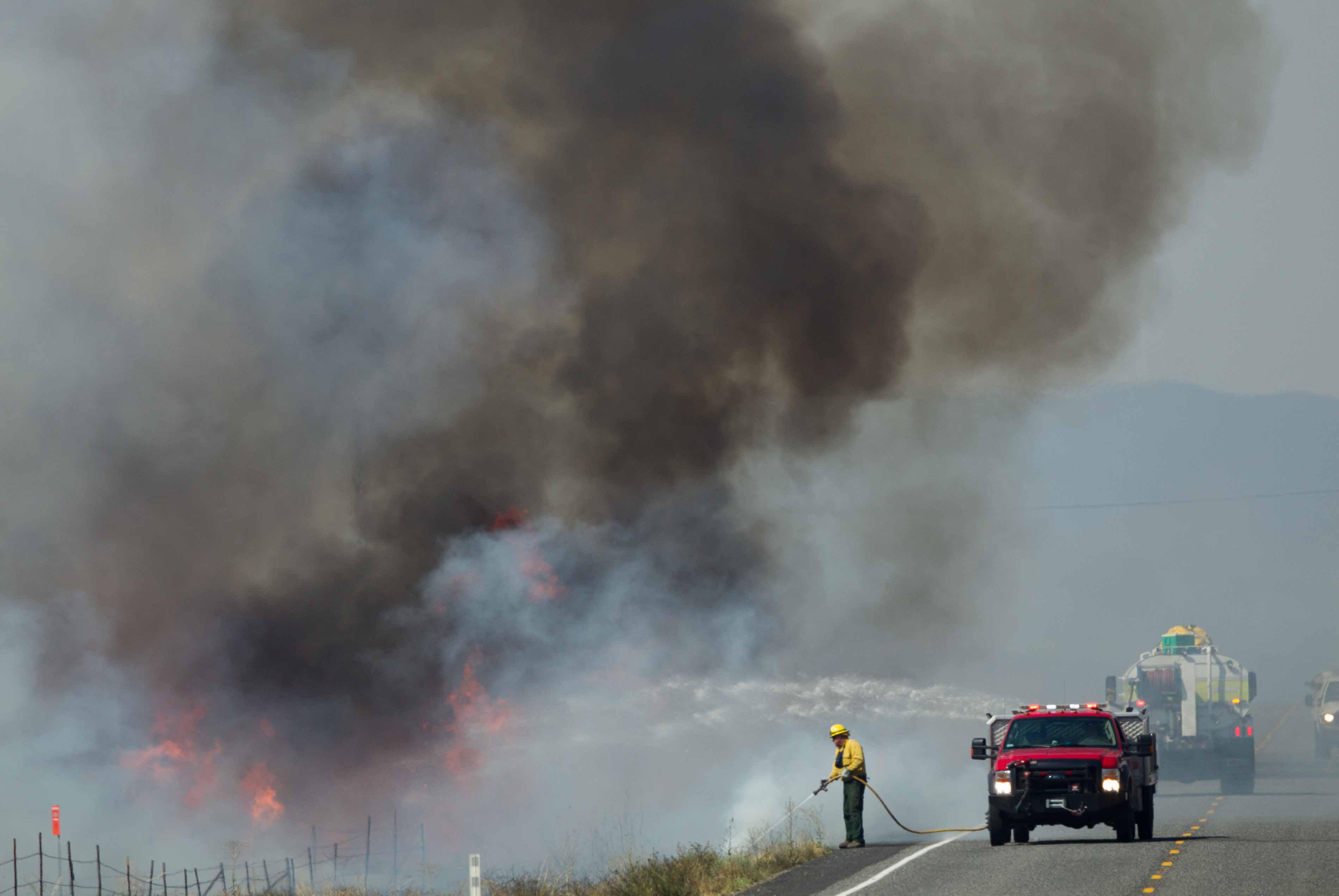 In this Sunday, July 31, 2016 photo, a wildfire burns between Moxee and Sunnyside, Wash.  (Sofia Jaramillo/Yakima Herald-Republic via AP)