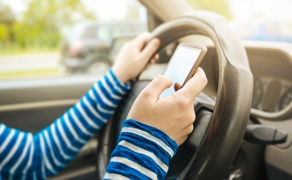 Woman driving car and texting message on smartphone_505920