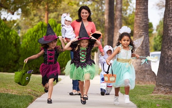 Parent Taking Children Trick Or Treating At Halloween_576001