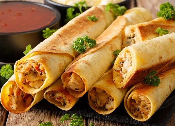 Baked taquitos with chicken and cheese close-up. horizontal_1540246017850