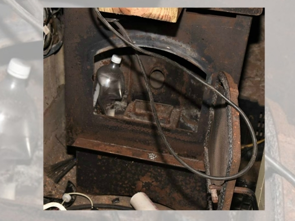 Photo of a charred wood stove and plastic soda bottle, believed used to cook methamphetamine.