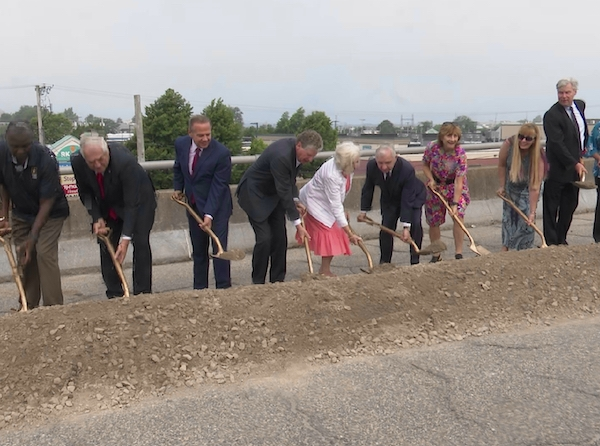Several Rhode Island dignitaries are lined up holding shovels for the camera at a patch of land near the Newport Pell Bridge.